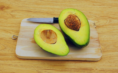 Fresh avocado on cutting board over wooden table