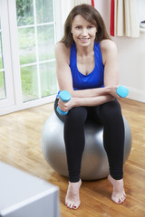 Woman Exercising In Front Of TV At Home