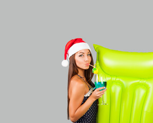 Girl in a swimsuit and Christmas hat with an inflatable mattress