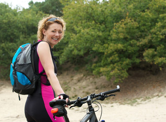 Middle aged woman smiling with bike