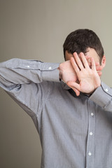 Young Caucasian man hiding his face with hands