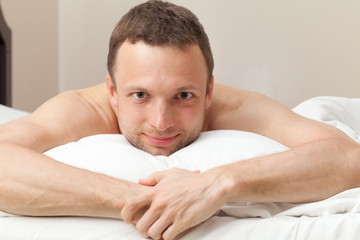 Portrait of smiling handsome Young Caucasian man in bed