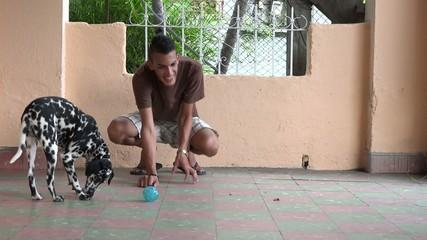 Young man playing with dalmatian pet