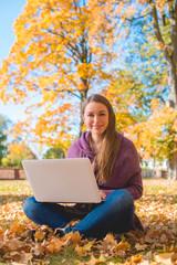 Pretty friendly woman sitting in an autumn park