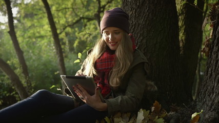 Young woman with tablet computer in beautiful autumn park.
