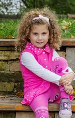 Fröhliches kleines Mädchen mit lockigem Haar