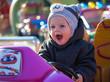 Happy little boy sitting in toy car