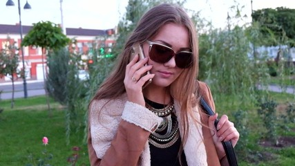 Women in sunglasses call by mobile phone