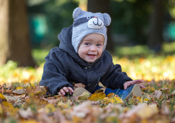 Happy baby sitting on the fallen leaves outdoors