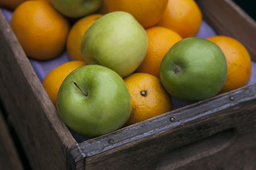 apples and oranges in wooden box