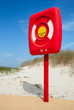 Постер, плакат: Safety life buoy in red case stand on the beach