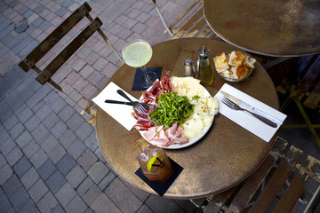 Ham, cheese and green salad on a plate at the terrace of a Frenc