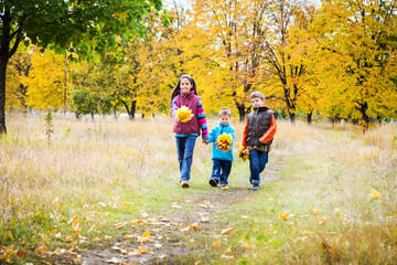 Three kids walking in autumn park