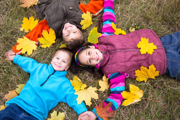 Three kids on yellow leaves