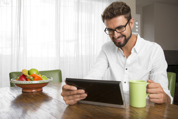 Hispanic male with a beard using the internet at home
