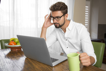 Focused man reading information on his laptop