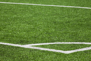 Football playing field background with green grass and white cor