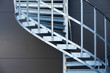 Fragmetn of modern metal spiral staircase above dark gray wall - 71247731