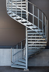 Modern metal spiral staircase above dark gray wall