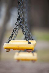 Empty yellow plastic swings on a playground