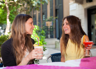 Portrait of two female young friends drinking a cocktail