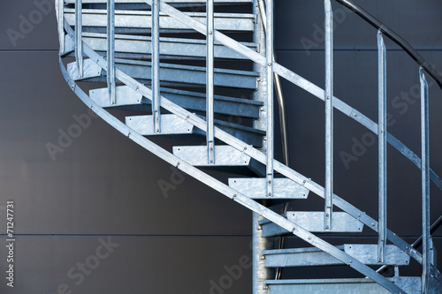 Fragmetn of modern metal spiral staircase above dark gray wall