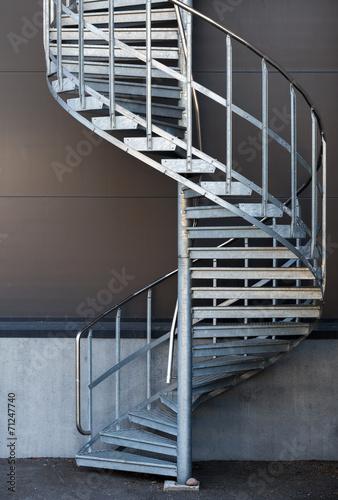 Modern metal spiral staircase above dark gray wall - 71247740