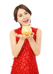 young woman holding a golden piggy bank . happy chinese new year