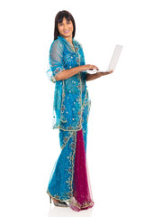 young indian woman in saree using laptop