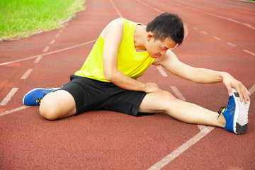 young man sitting on the track and stretching his leg
