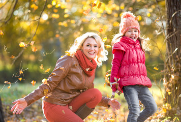 Happy parent and kid outdoor playing with autumn yellow leaves