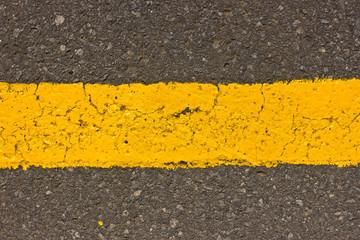 Yellow line painted on asphalt texture.