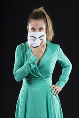 Anonymous girl with mask in a green dress