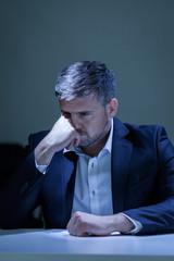 Depressed elegant man sitting at the table