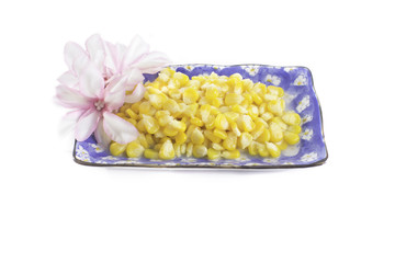 tinned corn in a transparent bowl on a white background