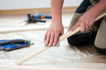 Using sandpaper for polishing wooden plank