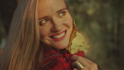 Young blonde woman smiling in autumn park.