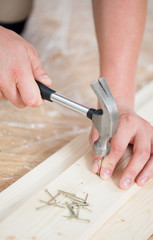Hammering nails into wooden board