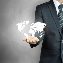 Businessman hand carrying world map - world domination concept