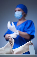 Nurse and dead body in morgue