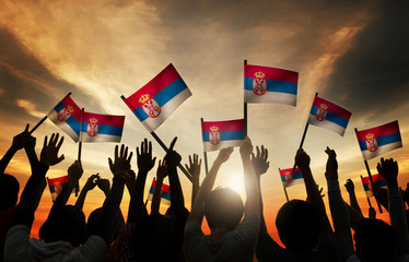 Group of People Waving Flag of Serbia in Back Lit