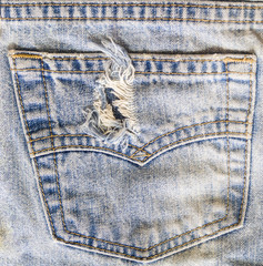 torn blue jeans back pocket