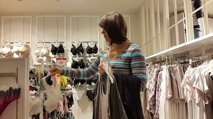 Young woman chooses a bra in lingerie store