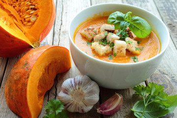 Pumpkin soup in a bowl with fresh herbs