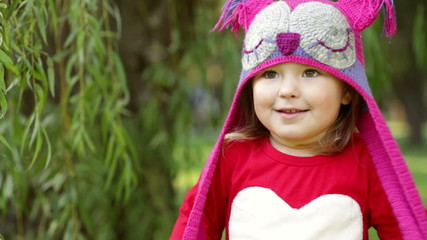 Beautiful laughing little toddler girl in a red coat