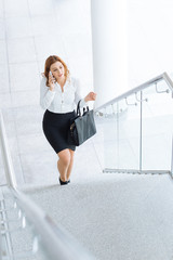 Businesswoman talking on cell phone while walking upstairs