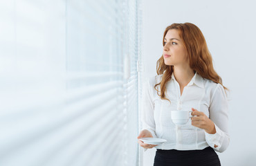 Dreamy businesswoman drinking coffee and looking through window