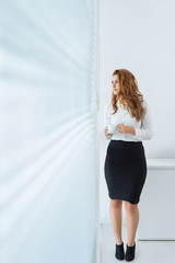 Beautiful female office worker looking through the window