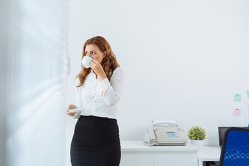 Young businesswoman drinking coffee