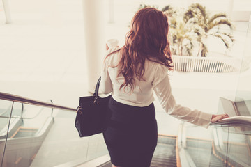 Rear view of businesswoman going down the escalator